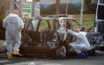 Illustrative: Members of the Israel police bomb squad investigate a car which exploded in the city of Petah Tikvah, February 3, 2014. (Photo credit: Gideon Markowicz/Flash90)