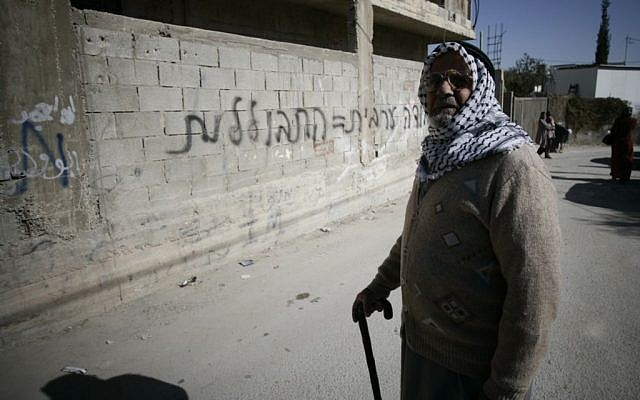 A resident of an East Jerusalem neighborhood walks past graffiti 'Arab labor = assimilation,' Monday, February 10, 2014 (photo credit: Flash90)
