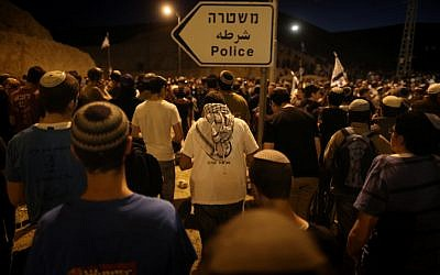 Israelis settlers and right-wing activists hold evening prayers after attending a march in the area known as E1 near the Israeli settlement of Ma'ale Adumim, on February 13, 2014. (photo credit: Yonatan Sindel/Flash90)