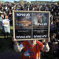 A man holds up a sign reading: 'We don't forget, we won't forgive' during a march in the area known as E1 near the Israeli settlement of Ma'ale Adumim on February 13, 2014. (photo credit: Yonatan Sindel/Flash90)
