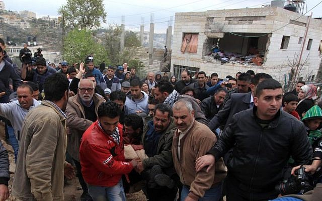Palestinian residents evacuate the body of Mu'taz Washha from his house toward an ambulance after he was killed during a reported Israeli army operation, in the West Bank town of Bir Zeit, Thursday, Feb. 27, 2014 (photo credit: Issam Rimawi/Flash90)