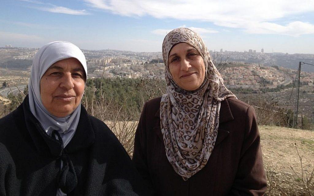 Nawal Barakat (r) and her neighbor 'Aaida stand with a backdrop of the northern Jerusalem neighborhood of Ramot, January 31, 2014 (photo credit: Elhanan Miller/Times of Israel)