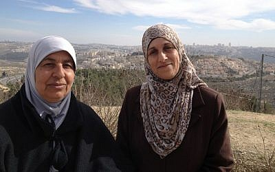 Nawal Barakat (r) and her neighbor 'Aaida stand with a backdrop of the northern Jerusalem neighborhood of Ramot, January 31, 2014 (photo credit: Elhanan Miller/Times of Israel)