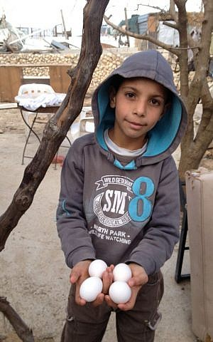 A local child displays the eggs laid by the hens recently smuggled into the village (photo credit: Elhanan Miller/TOI)