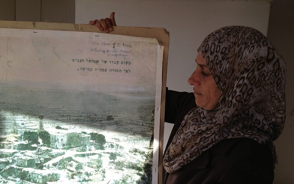 Nawal Barakat presents an aerial photo of Nabi Samwil predating 1971, when 30 homes surrounding the mosque were demolished by the IDF (photo credit: Elhanan Miller/TOI)