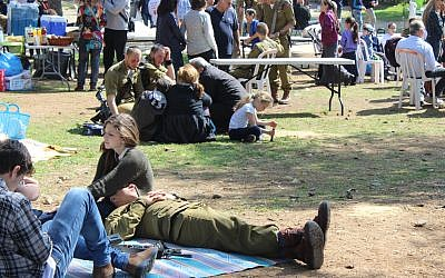Following a grueling 50-kilometer, all-night march, paratroopers relax with their families Feb 18. before the ceremony that awarded them their red berets. (The Times of Israel/Rebecca McKinsey)