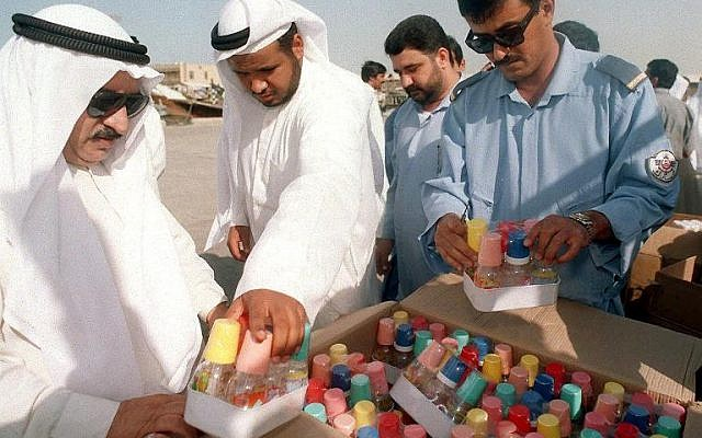 Kuwaiti coastguard officers examine smuggled cargo (photo credit: AFP/File Raed Qutena)