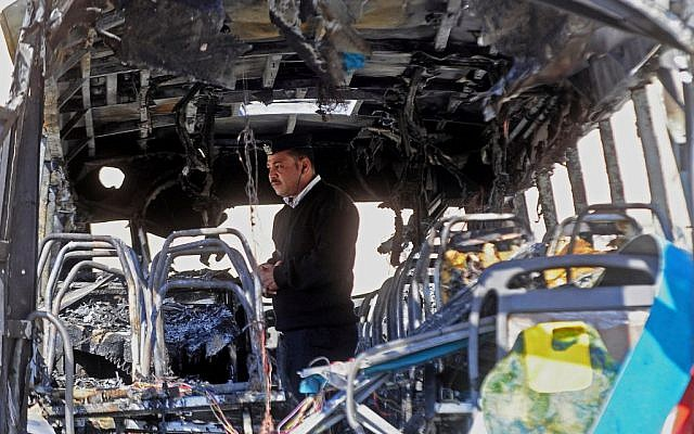 An Egyptian policeman inspects a damaged bus after a deadly explosion Sunday near the Egyptian border crossing with Israel in Taba, Egypt, Monday, Feb. 17, 2014. (photo credit: AP/Nameer Galal)