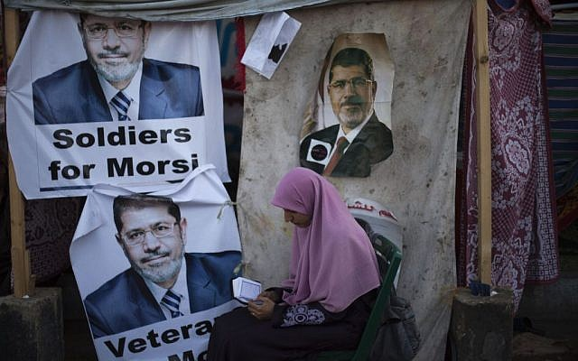 A supporter of Egypt's ousted president Mohammed Morsi reads the Quran as she sits next to a tent with posters of Morsi in Cairo, Egypt, in August.  (photo credit: AP/Khalil Hamra)