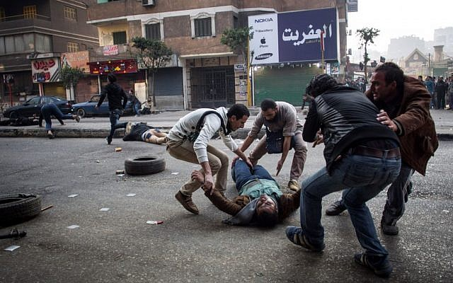 A mortally wounded supporter of Egypt's ousted Islamist president is evacuated as another wounded protester lies in the street during clashes with security forces in the Mohandiseen district of Cairo, Egypt. January 25, 2014. (photo credit: AP Photo/Eman Helal, File)