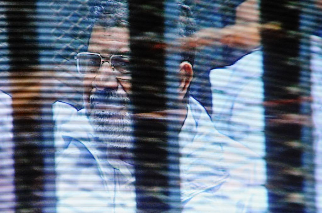 Egypt's ousted president Mohammed Morsi in a soundproof barred glass cage is seen on a monitor. Morsi and 35 others are facing charges of conspiring with foreign groups and undermining national security. (AP Photo/Mohammed al-Law, File)
