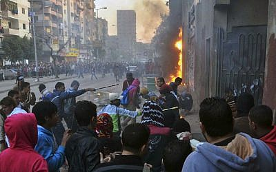 Supporters of Egypt's ousted President Mohammed Morsi damage a police building in Cairo's Ain Shams district, Egypt, Friday, Feb. 7, 2014. (photo credit: AP/Mostafa Darwish)