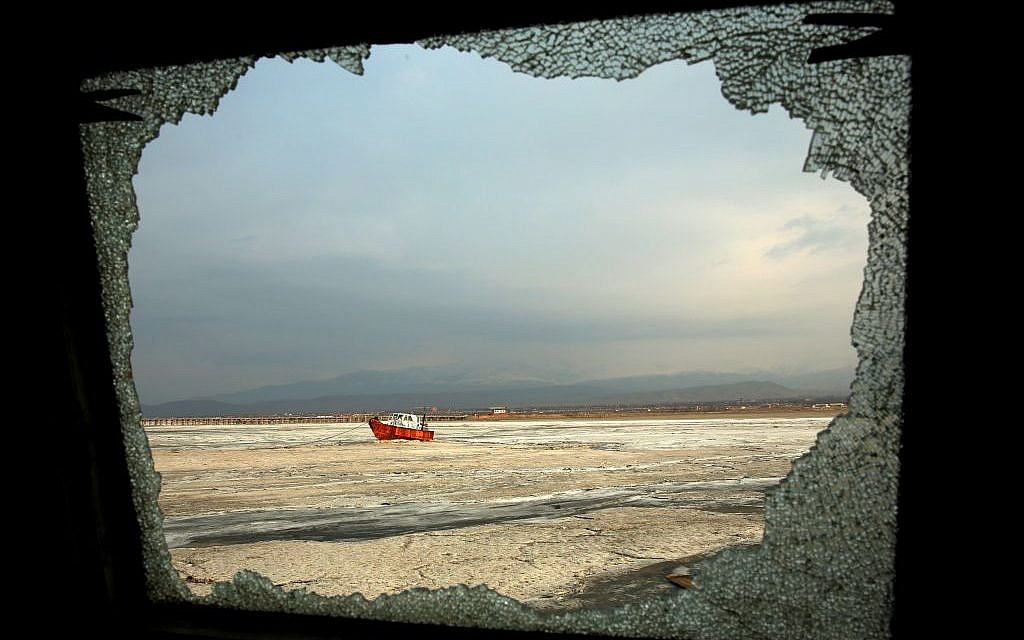 In this Sunday, Feb. 16, 2014 photo, an abandoned boat is seen through the shattered window of an abandoned ship, both stuck in solidified salt at Lake Oroumieh, northwestern Iran. (photo credit: AP Photo/Ebrahim Noroozi)
