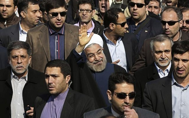 Escorted by his bodyguards, Iranian President Hassan Rouhani, center, waves to his well wishers as he attends an annual rally commemorating the anniversary of the 1979 Islamic revolution, in Tehran, Iran, on Tuesday, February 11, 2014. (photo credit: AP Photo/Vahid Salemi)