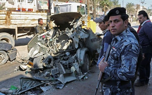 In this Thursday, Feb. 6, 2014 file photo, civilians and security forces inspect the site of a car bomb attack in the Shaab neighborhood of Baghdad, Iraq. Car bombs are one of the deadliest weapons used by the al-Qaeda breakaway group that dominates the Sunni insurgency in Iraq, with coordinated waves of explosions regularly leaving scores dead in Baghdad and elsewhere across the country. (photo credit: AP Photo/Karim Kadim, File)