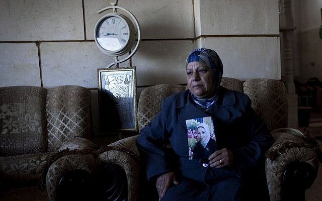 Palestinian Khadra al-Akhras poses with a photo of her late daughter Ayat al-Akhras, who blew herself up in a suicide bombing outside a Jerusalem supermarket in 2002, at the family house in the West Bank city of Bethlehem.  February 1, 2014 (photo credit: AP Photo/Nasser Nasser)