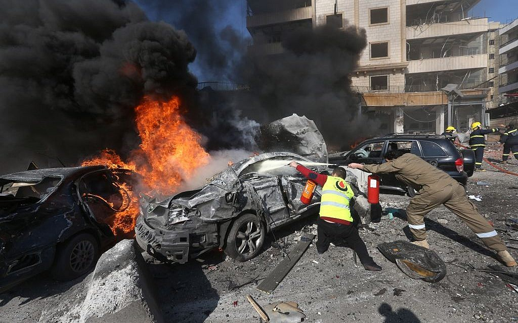 Lebanese firefighters extinguish burned cars at the site of an explosion, near the Kuwaiti Embassy and Iran's cultural center, in the suburb of Beir Hassan, Beirut, Lebanon, Wednesday, February 19, 2014 (photo credit: AP/Hussein Malla)