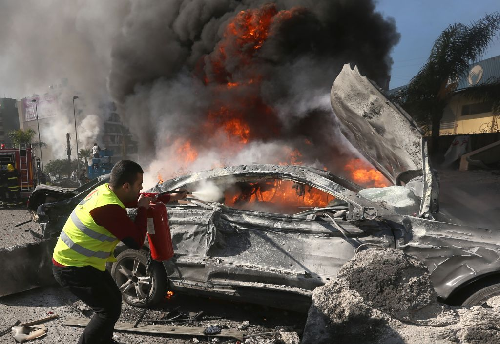 A Lebanese firefighter extinguishes a burned car at the site of an explosion near the Kuwaiti Embassy and Iran's cultural center, in the suburb of Beir Hassan, Beirut, Lebanon, Wednesday, February 19, 2014 (photo credit: AP/Hussein Malla)