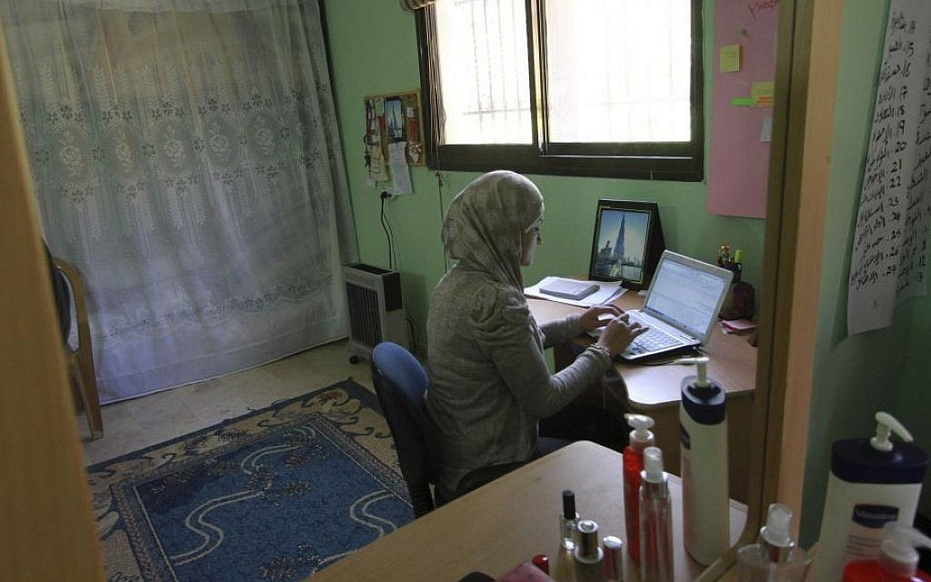 Abeer Abu Ghaith, who set up an internet employment brokerage and software development firm, is reflected in a mirror in her home while she works on her laptop in the West Bank village of Dura, Tuesday, Feb. 11, 2014. (photo credit: AP/Nasser Shiyoukhi)
