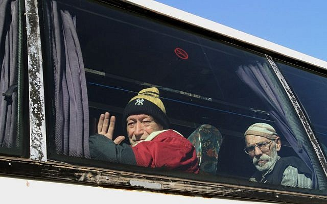 Men sitting on a bus pose for a photograph as they evacuate the battleground city of Homs, Syria, on Friday, February 7, 2014. (photo credit: AP Photo)