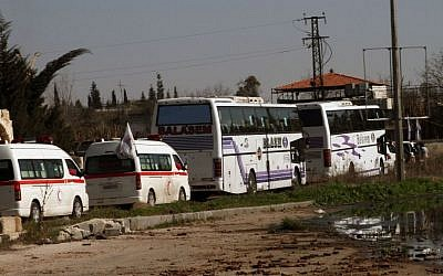 Syrian people on two buses followed by the Syrian Arab Red Crescent's vehicles evacuate the battleground city of Homs, Friday, February 7, 2014 (photo credit: AP)