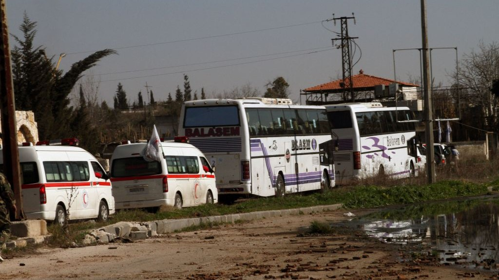 Syrian people on two buses followed by the Syrian Arab Red Crescent's vehicles evacuate the battleground city of Homs, Friday, Feb. 7, 2014 (photo credit: AP)