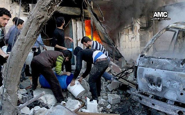 Syrian citizens fill water in a bucket to extinguish shops in flames caused by a Syrian government forces warplane attack, at al-Bab neighborhood in Aleppo, Syria, Saturday, Feb. 1, 2014 (AP Photo/Aleppo Media Center, AMC)