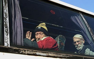 Elderly men sitting on a bus pose for a photograph as they evacuate the battleground city of Homs, Syria, on Friday, Feb. 7, 2014 (photo credit: AP)