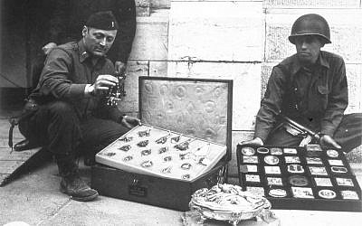 This photo provided by The Monuments Men Foundation for the Preservation of Art of Dallas, shows Monuments Man James Rorimer, left, and Sgt. Antonio Valim examining valuable art objects at Neuschwanstein Castle in Germany which were stolen from the Rothschild collection in France by the ERR and found in the castle in May of 1945. (AP Photo/National Archives and Records Administration)