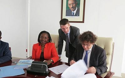 Chaim Motzen, managing director of Gigawatt Global (right), signs a power purchase agreement for a solar field in Rwanda at a ceremony in Kigali, Rwanda, as Eng. Emma Francoise Isumbingabo, Rwanda minister of state in charge of energy and water and local project manager Trevor Green of Remote Partners look on. (Photo credit: Courtesy)