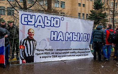 In this handout photo provided by Young Guards of United Russia party press service shows a group of demonstrators holding a banner with a photo of American Ice Hockey referee Brad Meier and message reading 'Turn the referee into soap.' (AP Photo/Voroshirin Dmitriy, Young Guards)