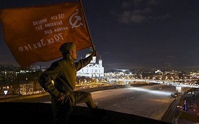 A man dressed in WWII-era Soviet Army uniform holds a replica of Soviet Victory Flag on a roof of TV Rain headquarters late Monday during a protest picket in Moscow. Several Russian cable and satellite providers have removed a top independent television channel from their packages after it ran a poll asking the audience if the Soviets should have surrendered Leningrad to the Nazis to avoid more than a million deaths during the WWII siege. (AP Photo/Mikhail Dukhovich)