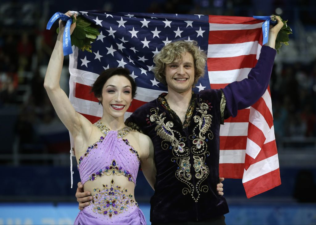 Meryl Davis, left, and Charlie White of the United States pose for photographers with the US flag after winning the gold medal in the ice dancing competition in Sochi, Russia, on Monday (photo credit: AP/Darron Cummings)