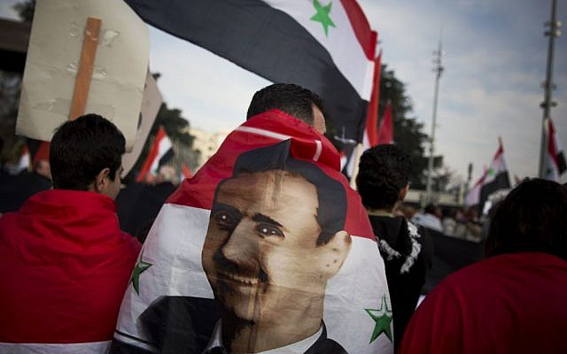 A Syrian demonstrator is wrapped in a Syrian flag carrying the picture of President Assad as they shout pro-government slogans during a demonstration outside the United Nations headquarters in Geneva, Switzerland, Friday Jan. 31, 2014. (photo credit: AP/Anja Niedringhaus)