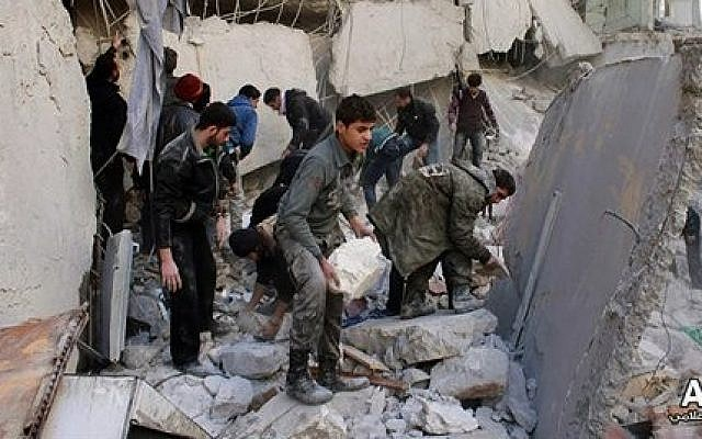 Syrians inspect the rubble of destroyed buildings following a government airstrike in Aleppo, Syria,  Jan. 31, 2014 (photo credit: AP /Aleppo Media Center, AMC)