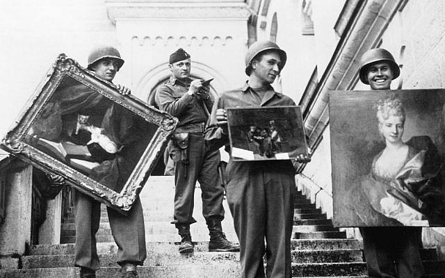 This photo provided by The Monuments Men Foundation for the Preservation of Art of Dallas, shows Monuments Man James Rorimer, with notepad, as he supervises American GI's hand-carrying paintings down the steps of the castle in Neuschwanstein, Germany in May of 1945. (photo credit: AP/National Archives and Records Administration)