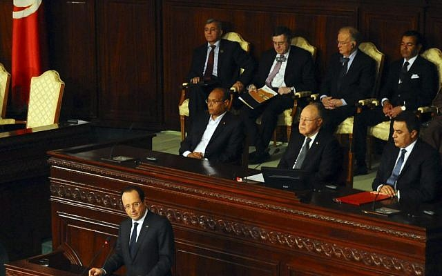French President Francois Hollande delivers his speech, as first row, from left, Tunisian President Moncef Marzouki, Assembly speaker Mustapha Ben Jaafar, and Tunisian Prime Minister Mehdi Jomaa, listen during a ceremony at the Constituent Assembly in Tunis, Friday, Feb. 7, 2014. (photo credit: AP/Hassene Dridi)