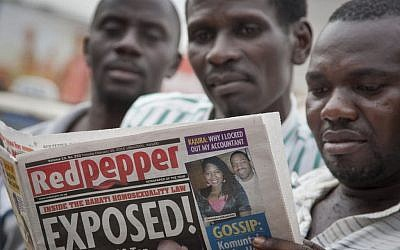 "A Ugandan reads a copy of the ""Red Pepper"" tabloid newspaper in Kampala, Uganda Tuesday, Feb. 25, 2014.  (photo credit: AP Photo/Rebecca Vassie)"