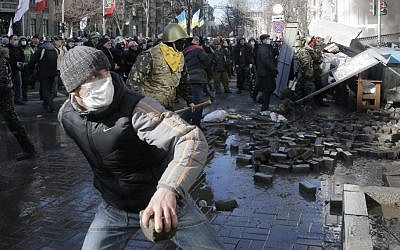 Anti-government protesters lob stones during clashes with riot police outside Ukraine's parliament in Kiev, Ukraine, Tuesday, Feb. 18, 2014. (AP Photo/Efrem Lukatsky)