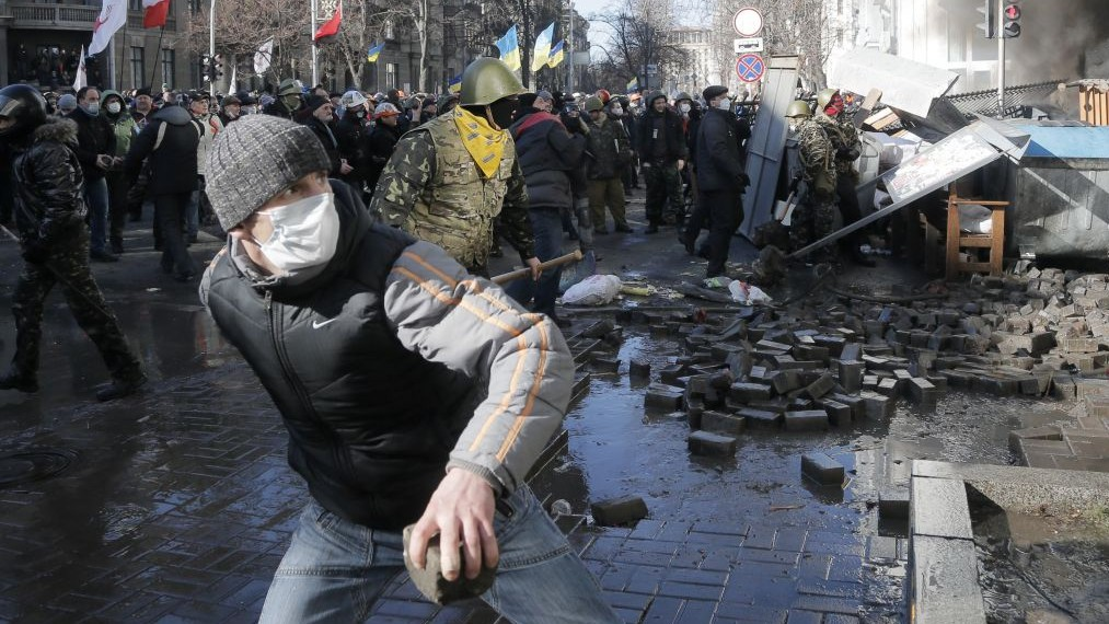 Anti-government protesters lob stones during clashes with riot police outside Ukraine's parliament in Kiev, Ukraine, Tuesday, Feb. 18, 2014. (photo credit: AP/Efrem Lukatsky)