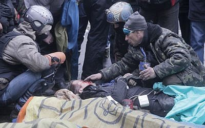 An activist closes a victim's eyes while others pay respects to protesters who were killed in clashes with police in Kiev's Independence Square, the epicenter of the country's current unrest, Thursday, February 20, 2014 (photo credit: AP/Efrem Lukatsky)