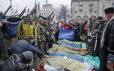 Activists and priests pay respects to protesters who were killed in clashes with police in Kiev, Ukraine, Thursday, February 20, 2014 (photo credit: AP/Efrem Lukatsky)