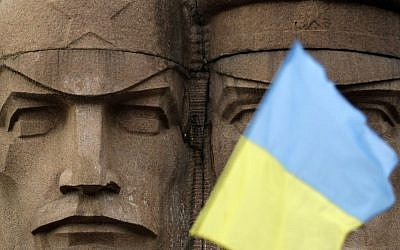A Ukrainian flag flies in front of the KGB officers monuments in Kiev, Ukraine, Sunday, Feb. 23, 2014.  (photo credit: AP Photo/Darko Vojinovic)