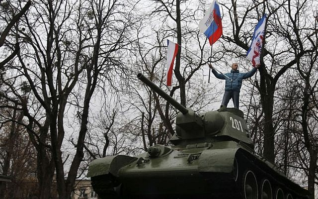 A Pro-Russian demonstrator waves Russian and Crimea flags from an old Soviet Army tank during a protest in front of a local government building in Simferopol, Crimea, Ukraine, on Thursday, February 27, 2014. (photo credit: AP Photo/Darko Vojinovic)