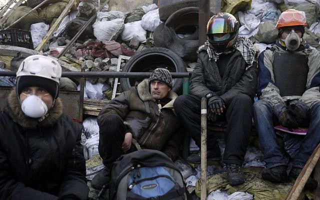 Anti-government protesters take a break on a barricade at Independence Square in Kiev, Ukraine, Friday, Feb. 21, 2014 (photo credit: AP/ Marko Drobnjakovic)