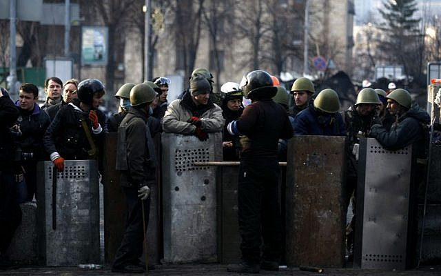 Anti-government protesters man a barricade on the outskirts of Independence Square in Kiev, Ukraine on Friday. (photo credit: AP Photo/ Marko Drobnjakovic)