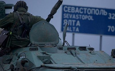 "A soldier rests atop a Russian armored personnel carrier with a road sign reading ""Sevastopol - 32 kilometers, Yalta - 70 kilometers"", near the town of Bakhchisarai, Ukraine, Friday, Feb. 28, 2014. (photo credit: AP/Ivan Sekretarev)"