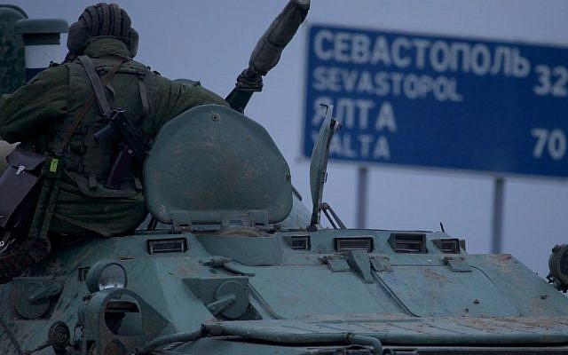 """A soldier rests atop a Russian armored personnel carrier with a road sign reading """"Sevastopol - 32 kilometers, Yalta - 70 kilometers"""", near the town of Bakhchisarai, Ukraine, Friday, Feb. 28, 2014. (photo credit: AP/Ivan Sekretarev)"""