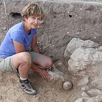 Archaeologist Diane Benton poses by the juglet filled with silver at the time of its discovery at Abel Beth Maacah. (photo credit: Robert Mullins)
