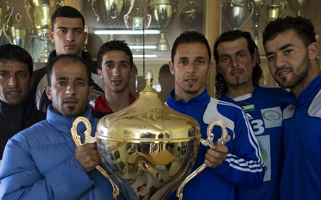 Abu Hammad family members pose with the Yasser Arafat Cup at their club's trophy room in the West Bank village of Wadi al-Nees.  (photo credit: AP Photo/Dusan Vranic)